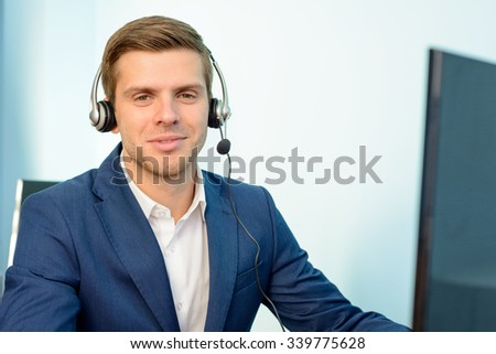 Young Customer Support Phone Operator with Headset at his Working Place in the Office. - stock photo