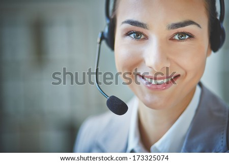 Young customer support representative looking at camera with smile - stock photo