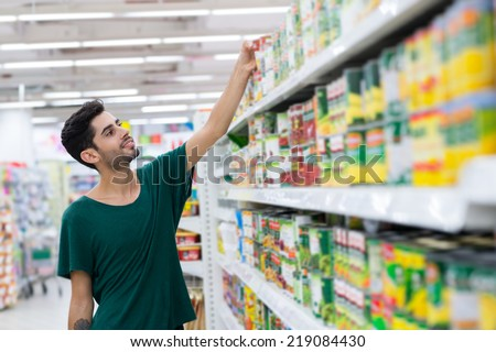 Young customer taking canned food from the shelf in the store - stock photo