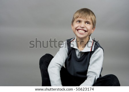 young cute and funny happy  blond boy making loud laugh sitting with brilliant  smile isolated over gray background - stock photo