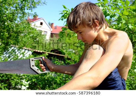 young cute athletic teenager boy works and repairs house roof with saw and hammer outdoor in