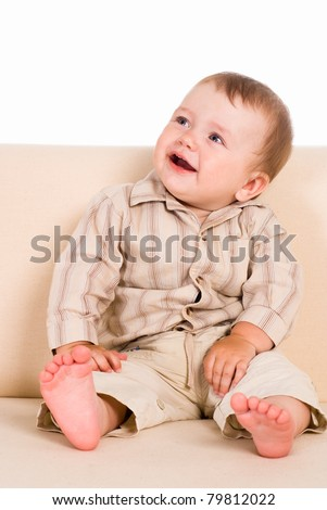 young cute baby sitting on a sofa