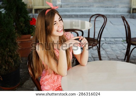 Young cute blond-brown girl sitting at the vintage cafe and laughing