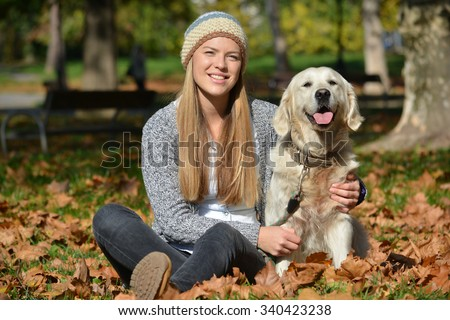 Young, cute blonde girl with her pet, retriever dog, sitting on the autumn leaves in a park
