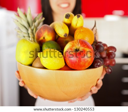 Young cute brunette girl holding a dish full of fruits beginning her diet.