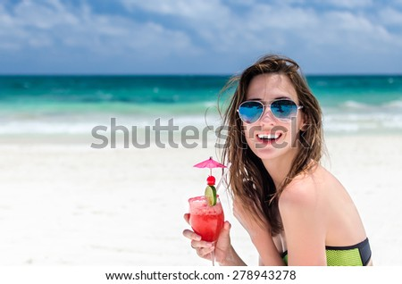 Young cute caucasian woman drinking fresh delicious cocktail with tequila, lime and strawberry at tropical white sandy beach during her Caribbean vacation in Tulum, Mexico - stock photo