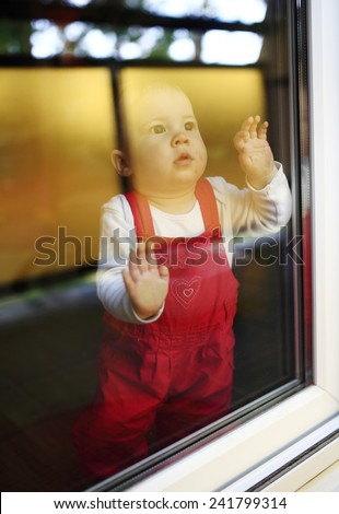 Young cute child sitting at window - stock photo
