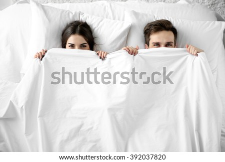 Young cute couple lying together in bed. - stock photo
