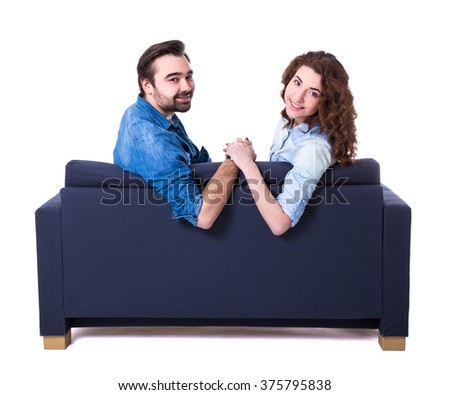 young cute couple sitting on sofa isolated on white background - stock photo