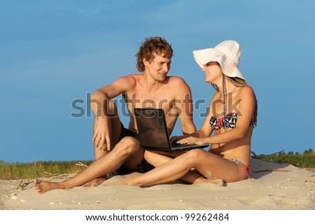 Young cute couple with laptop on beach. - stock photo