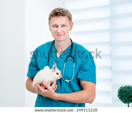 Young cute doctor veterenarii in the green uniform with a rabbit in his hands - stock photo
