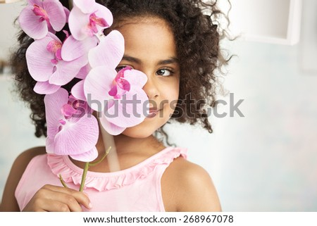 Young cute girl holding an orchid - stock photo