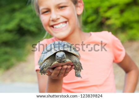 Young cute girl holding turtle. Focus on the turtle. - stock photo