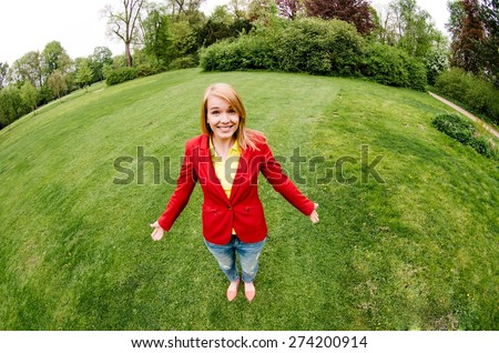 Young cute girl in green spring park. Fisheye extra wide angle shot. - stock photo