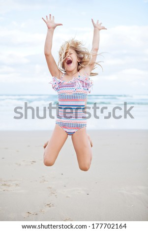 Young cute girl in swimming suit having fun at the beach by jumping in air - stock photo