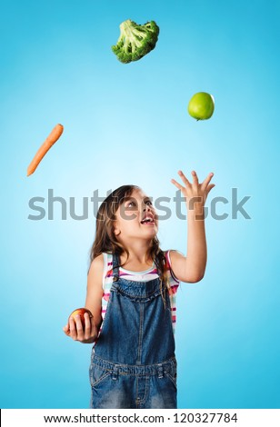Young cute girl juggling vegetables and fruit over her head, healthy lifestyle, eating and diet concept - stock photo