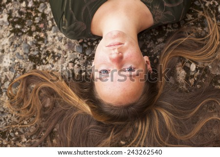 Young cute girl lying on the pavement with her long hair, top view close-up. - stock photo