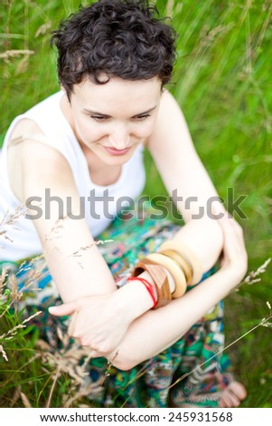 young cute girl resting on fresh spring grass  - stock photo