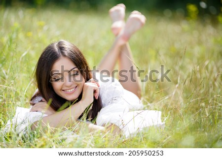 Young cute girl resting on soft pillow in fresh spring grass. Young woman sleeping on soft pillow in fresh spring grass. smiling woman portrait outdoors.