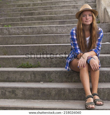 Young cute girl sitting on the stone steps of the street. European vacation. - stock photo