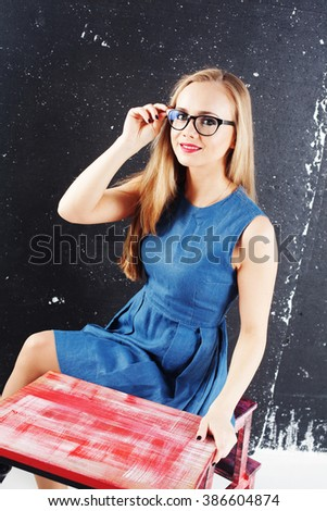Young cute girl student teacher in the classroom at a desk in a dress chalk board, training, MBA, courses, trainings, education, business, manager, office, - stock photo