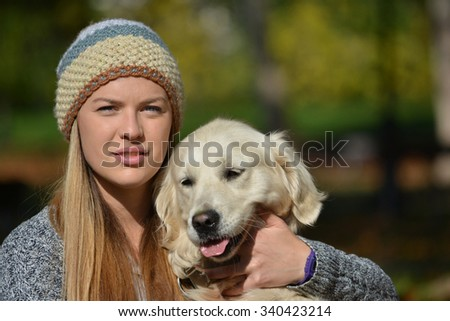 Young, cute girl wearing cardigan and woolen cap, standing in autumn leaves in a park together with her pet, golden retriever dog
