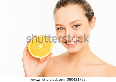 Young cute girl with nice smile and orange slice - stock photo