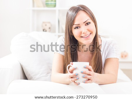 Young cute happy woman lie on bed in living room with cup in hands smiling