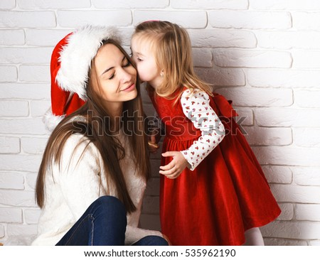 young cute little blonde girl in christmas red dress kissing her smiling mother in xmas hat and long brunette hair on white brick wall background