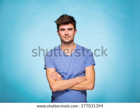 young cute man on standing on blue background - stock photo