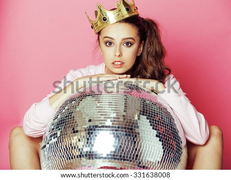 young cute party girl on pink background with  ball and crown smiling