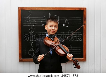 Young cute schoolboy holding the violin at the blackboard with musical notes - stock photo