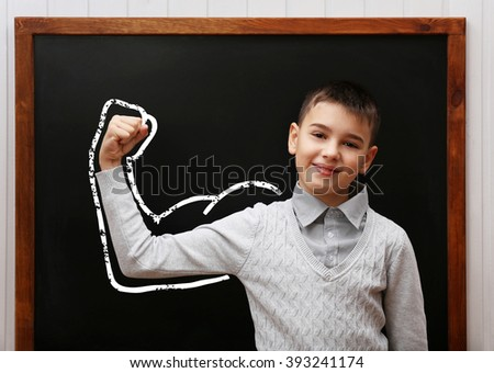 Young cute schoolboy standing at the blackboard - stock photo