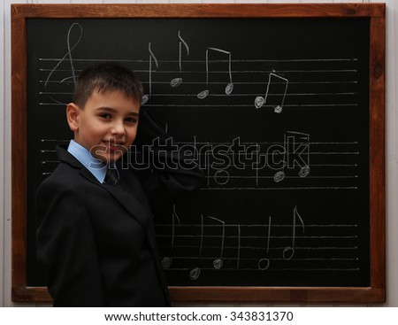 Young cute schoolboy standing at the blackboard with musical notes - stock photo