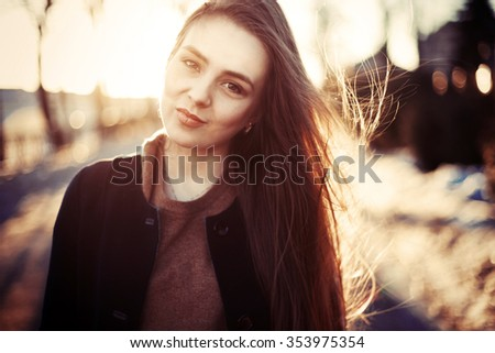 Young cute sensual smiling brunette woman posing in spring evening sunny weather on the street