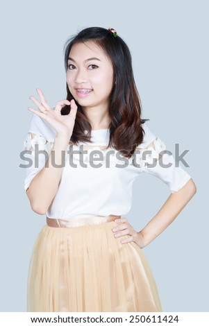Young cute smiling girl showing OK sign