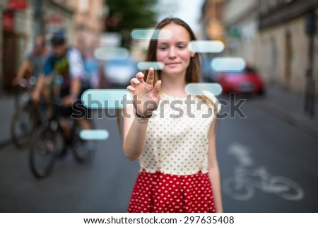 Young cute teen girl in the street presses an imaginary button in the air. Buttons with place for your text. - stock photo