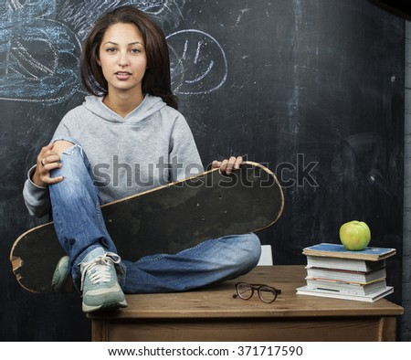 young cute teenage girl in classroom at blackboard seating on table smiling - stock photo