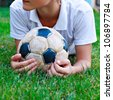 Young cute teenager lying on grass with old soccer ball - stock photo