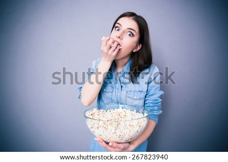 Young cute woman eating popcorn over gray background. Looking at camera - stock photo
