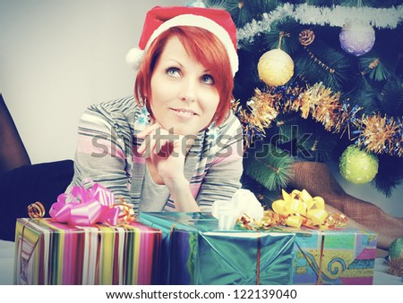 Young cute woman in a Christmas hat with gifts and Christmas tree - stock photo