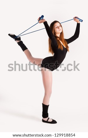 Young cute woman in gymnast suit show athletic skill at white background - stock photo