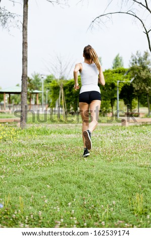Young cute woman jogging in city park