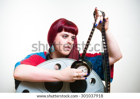 Young cute woman looking at 35 mm movie filmstrip with cinema reel on white background