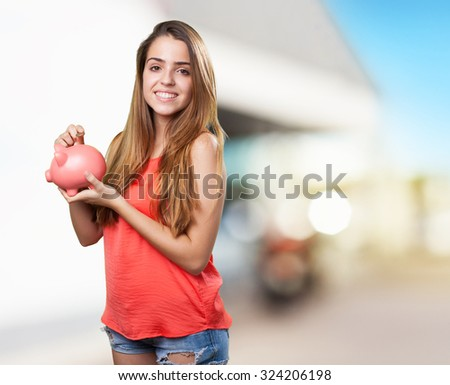 young cute woman saving with a piggy bank - stock photo