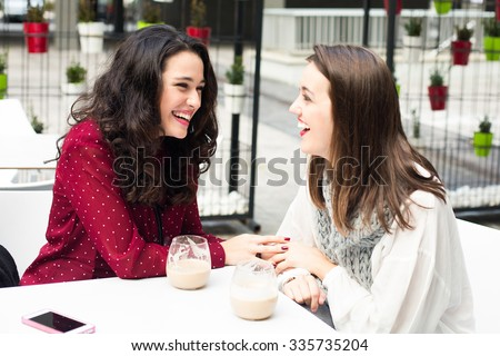 Young cute women laughing while having a coffee outdoors - stock photo