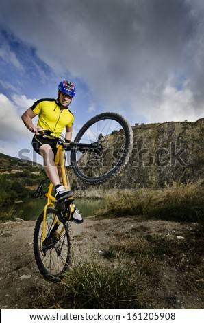 Young cyclist back the front wheel of your bike. - stock photo