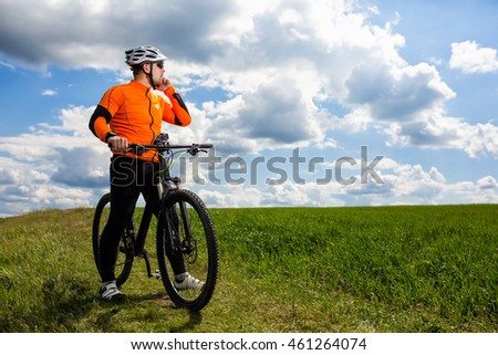 Young Cyclist In Orange Shirt Checks His Phone