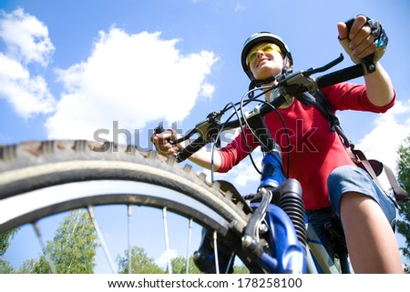 Young cyclist on a mountain bike and the blue sky in the park - stock photo