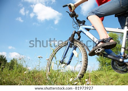 Young cyclist on a mountain bike and the blue sky in the park